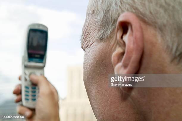 Mature businessman using camera phone, close-up, side view