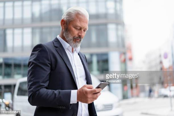 mature businessman using cell phone in the city - portable information device stock-fotos und bilder