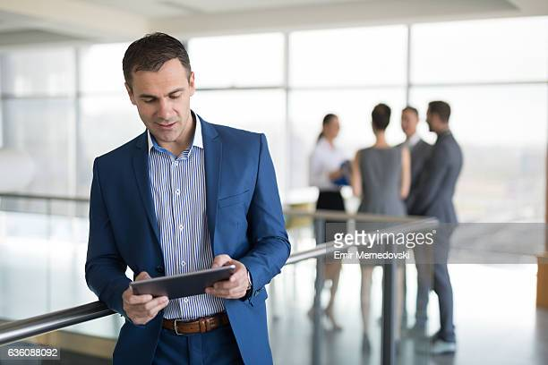 mature businessman using digital tablet in office building hallway. - personas en el fondo fotografías e imágenes de stock