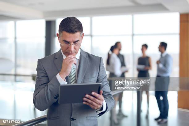 Mature businessman using digital tablet in office building hallway.