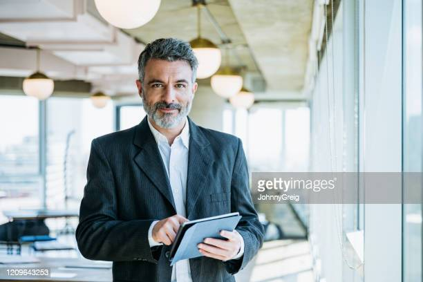 mature businessman using digital tablet in office - businessman stock pictures, royalty-free photos & images