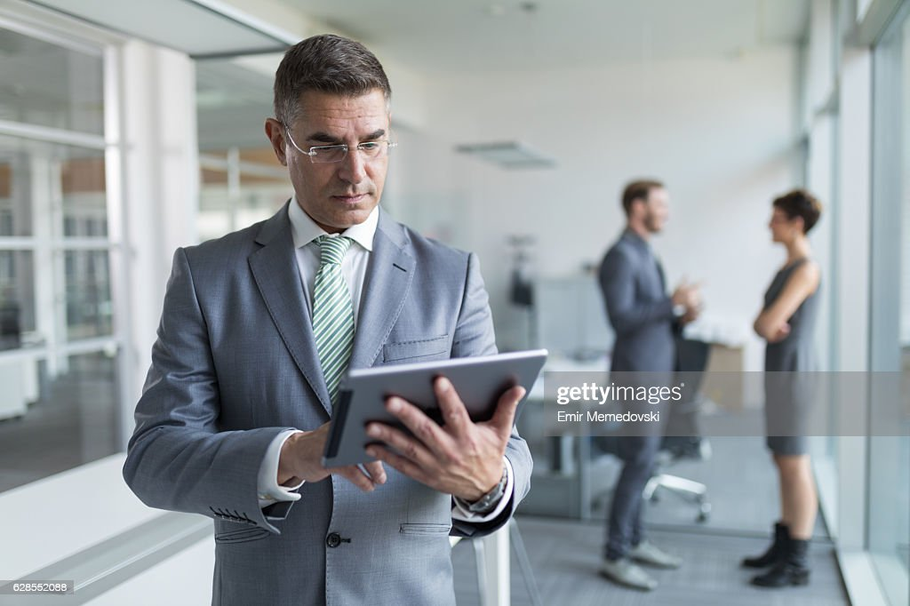 Mature businessman using digital tablet in the office : Stock Photo