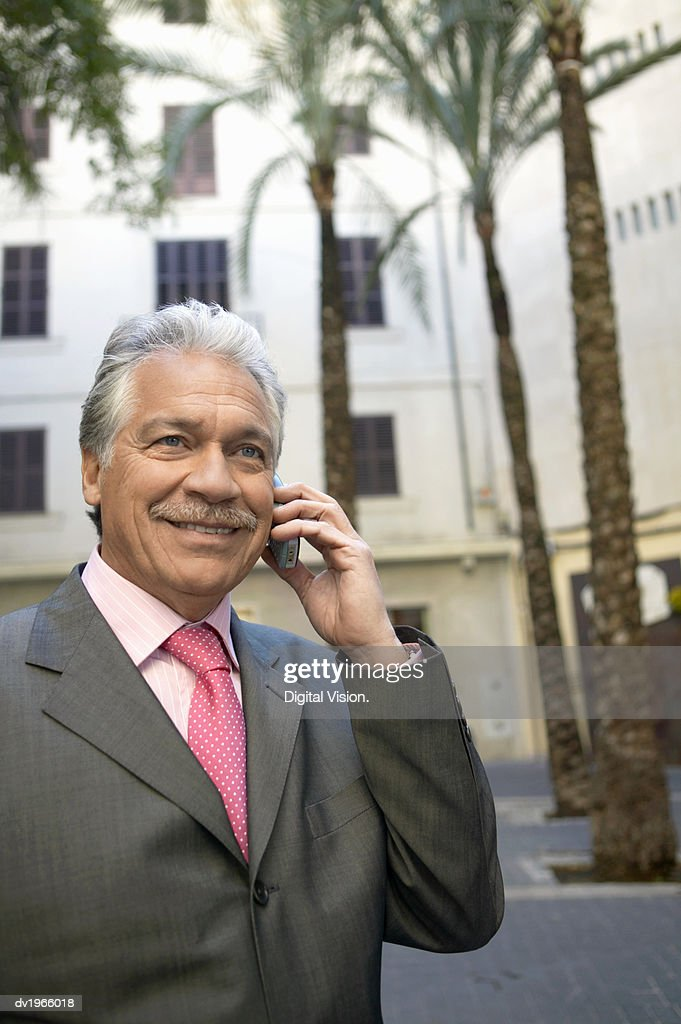 Mature Businessman Using His Mobile Phone in the City : Stock Photo