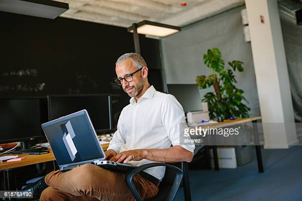 Mature businessman using laptop at startup