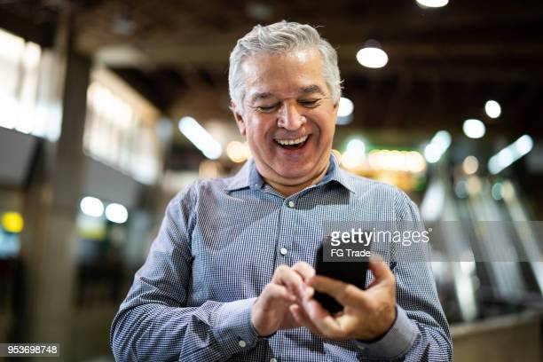 mature businessman using mobile phone at airport - brazilian men stock photos and pictures