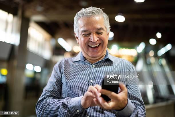 oudere zakenman met behulp van mobiele telefoon op luchthaven - mobile stockfoto's en -beelden