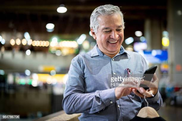 mature businessman using mobile phone at airport - one senior man only stock pictures, royalty-free photos & images