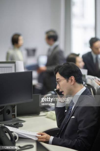 mature businessman using mobile phone at desk - incidental people stock pictures, royalty-free photos & images