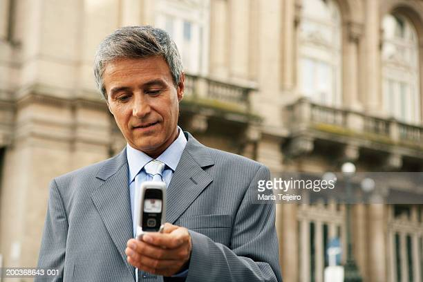 Mature businessman using mobile phone, close up