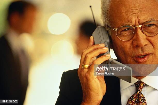 Mature businessman using mobile phone, close-up