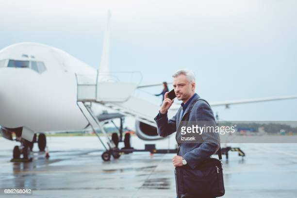 Mature businessman using mobile phone on airport