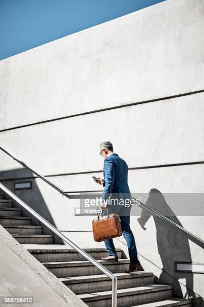 mature businessman using mobile phone on steps - staircase stock photos and pictures