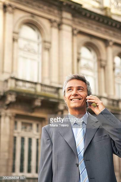 成熟したビジネスマンが携帯電話を使用して笑う