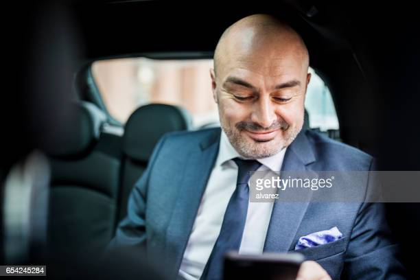 Mature businessman using mobile phone while traveling by car