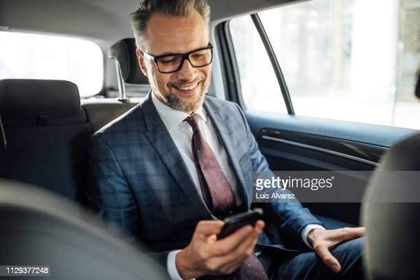 mature businessman using phone in car commute - alta sociedad fotografías e imágenes de stock