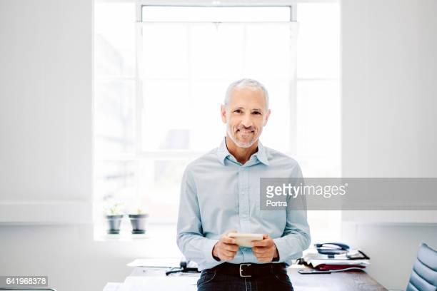 rijpe zakenman met behulp van slimme telefoon in kantoor - fel verlicht stockfoto's en -beelden