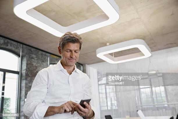 mature businessman using smartphone in modern office - vestimenta de negocios fotografías e imágenes de stock