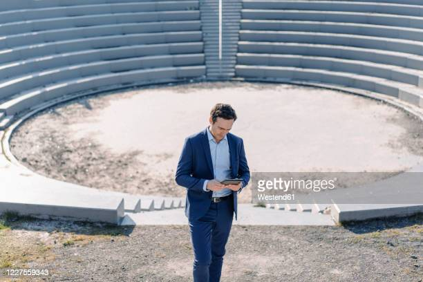 mature businessman using tablet at an amphitheatre on a disused mine tip site - amphitheatre stock pictures, royalty-free photos & images