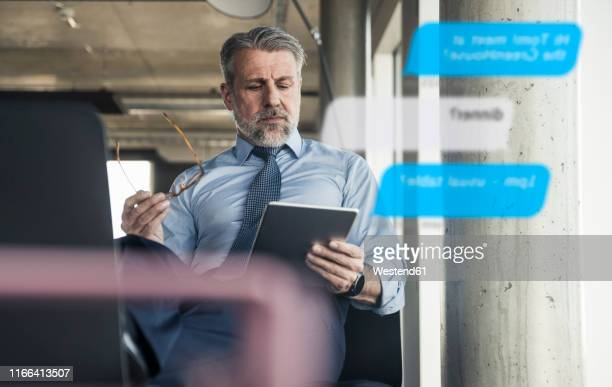 mature businessman using tablet for messaging in the office - mensajería instantánea fotografías e imágenes de stock