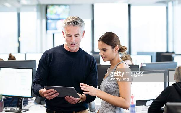 Mature businessman using tablet with young Aboriginal Australian woman