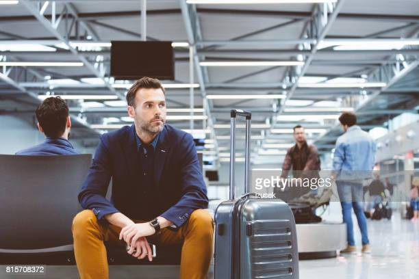 Mature businessman waiting for flight at airport lounge