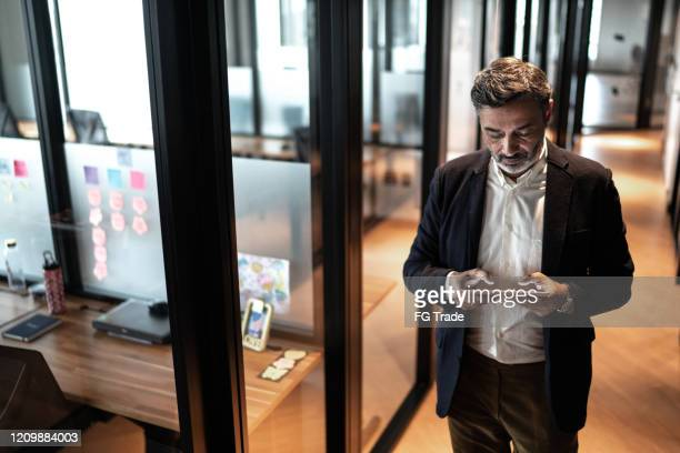mature businessman walking and using digital tablet at corridor office - businesswear stock pictures, royalty-free photos & images