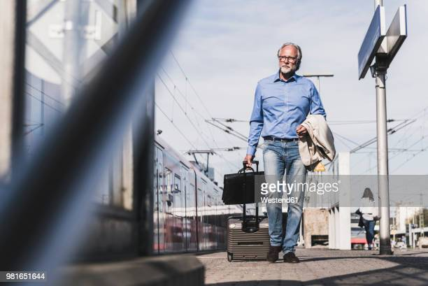 mature businessman walking at train platform with suitcase and briefcase - ジーンズ ストックフォトと画像