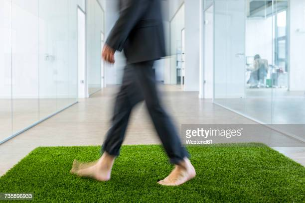 Mature businessman walking barefoot on grass carpet in office