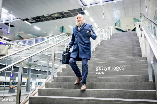 mature businessman walking down the stairs at metro station - railings stock photos and pictures
