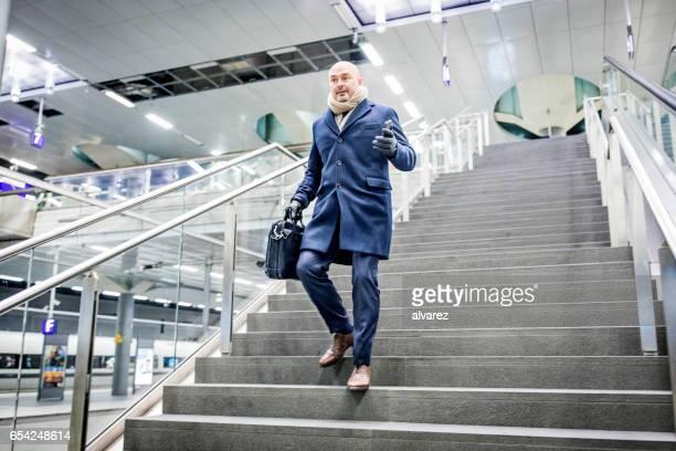Reife Geschäftsmann zu Fuß die Treppe hinunter in die u-Bahnstation