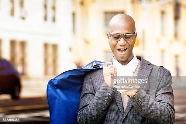 Mature businessman walking home with dry cleaning and phone