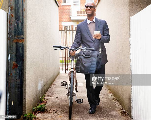 Mature businessman walking home with his bicycle and phone