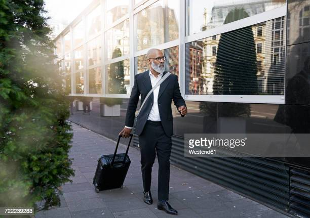 Mature businessman walking in street, pulling trolley bag