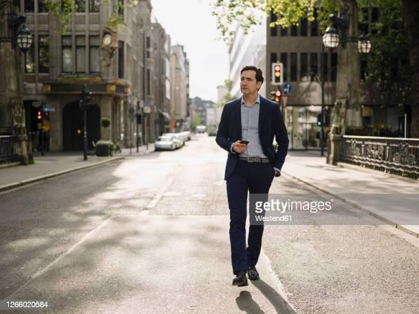 mature businessman walking on a city street holding smartphone - walking stock-fotos und bilder