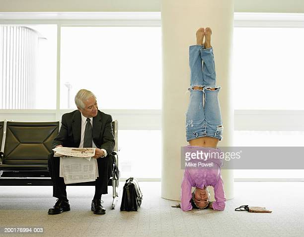 Mature businessman watching young woman doing yoga in airport lounge