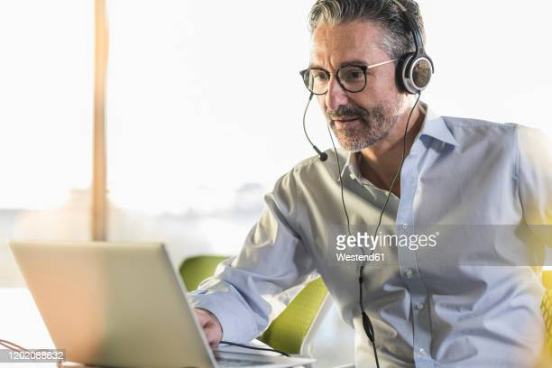 mature businessman wearing headphones using laptop at desk in office - video conference stock pictures, royalty-free photos & images