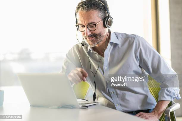 mature businessman wearing headphones using laptop at desk in office - conference call stock pictures, royalty-free photos & images
