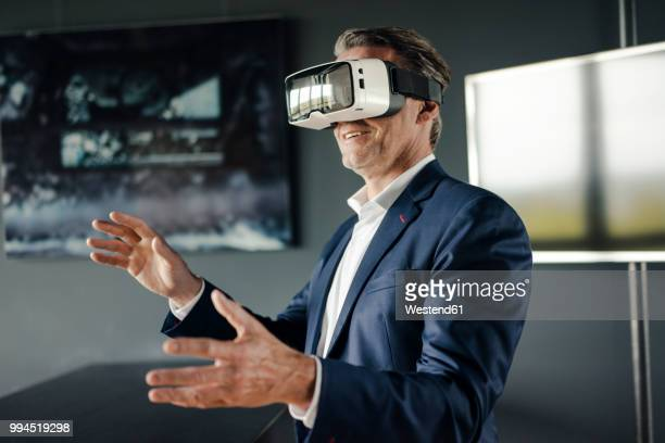 mature businessman wearing vr glasses in office - simulatore di realtà virtuale foto e immagini stock