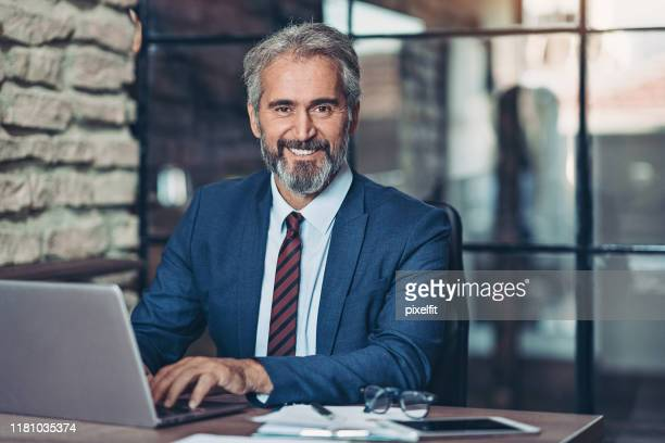 homme d'affaires mûr avec un ordinateur portatif - expertise photos et images de collection