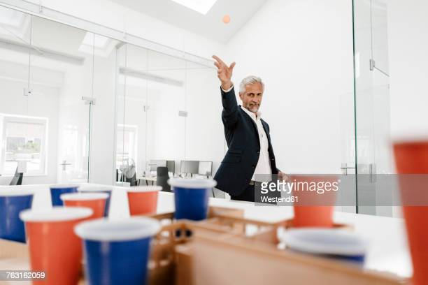 mature businessman with architectural model in office throwing a ball - lanciare foto e immagini stock