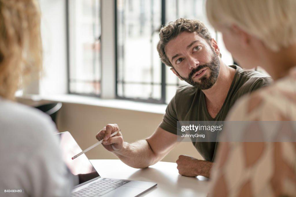Homem de negócios maduro com barba apontando para portátil com lápis e ouvir a colega : Foto de stock