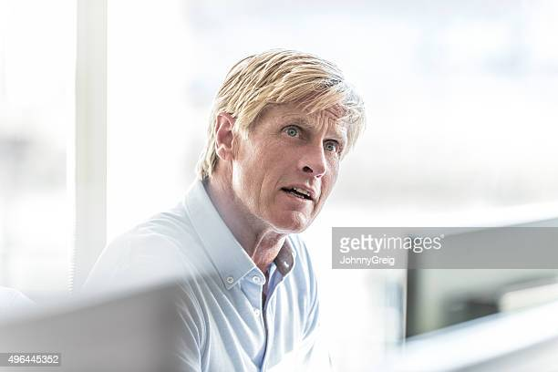 Mature businessman with blonde hair in office, looking away
