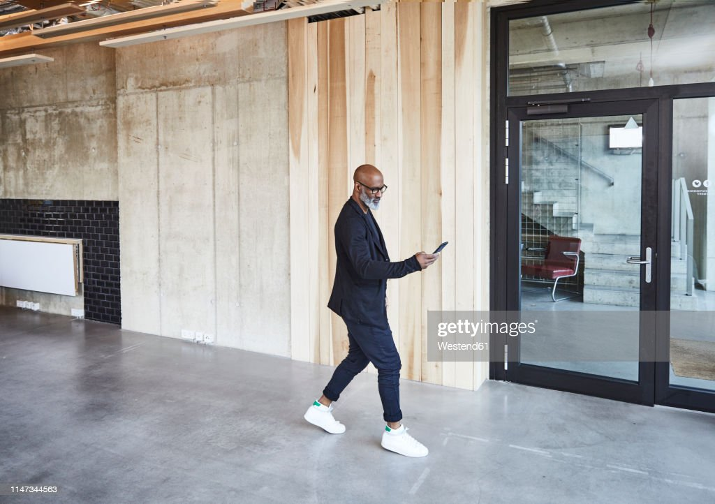 Mature Businessman With Cell Phone Walking In Modern Office High Res Stock Photo Getty Images