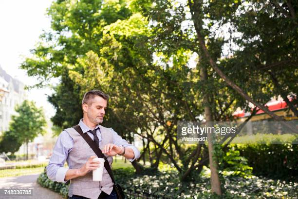 Mature businessman with coffee in city park checking the time
