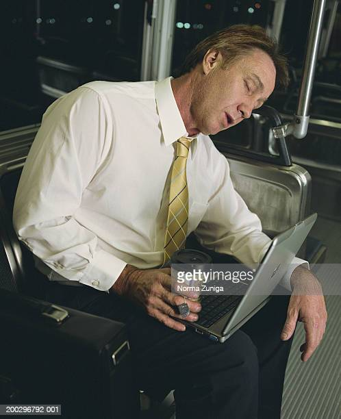 Mature businessman with laptop computer sleeping on bus