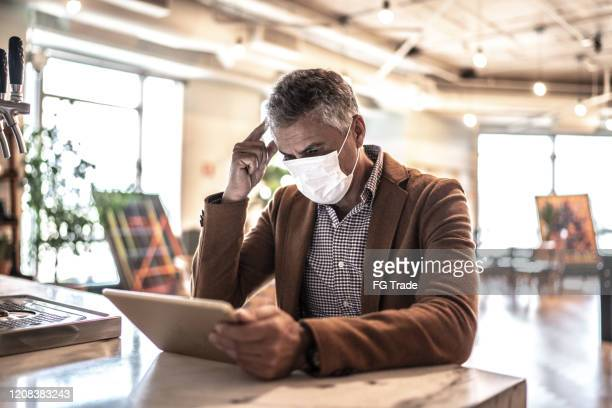 mature businessman with mask using digital tablet at work - crisis stock pictures, royalty-free photos & images
