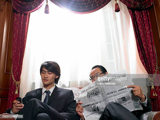 Mature businessman with newspaper looking at young man's mobile phone