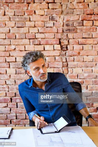 Mature businessman with plan and notebook working at desk in office