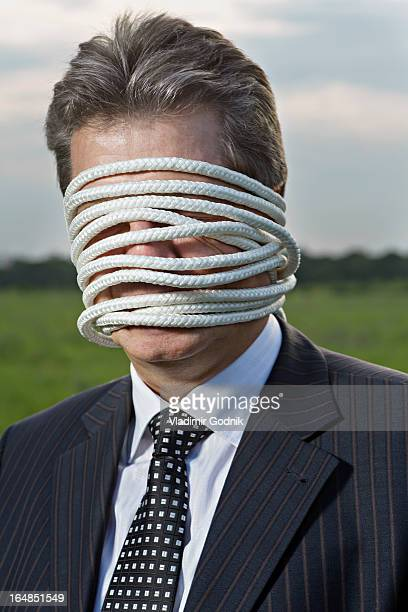 a mature businessman with rope wrapped around his face - sadomasoquismo fotografías e imágenes de stock