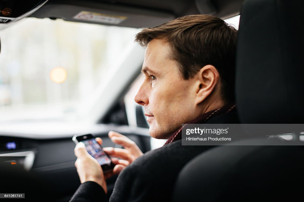 Mature Businessman with Smart phone in a taxi : Foto de stock